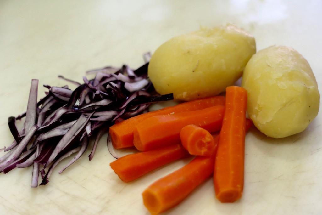 Deja enfríar y pélalas. Corta la cebolla morada en gajos.